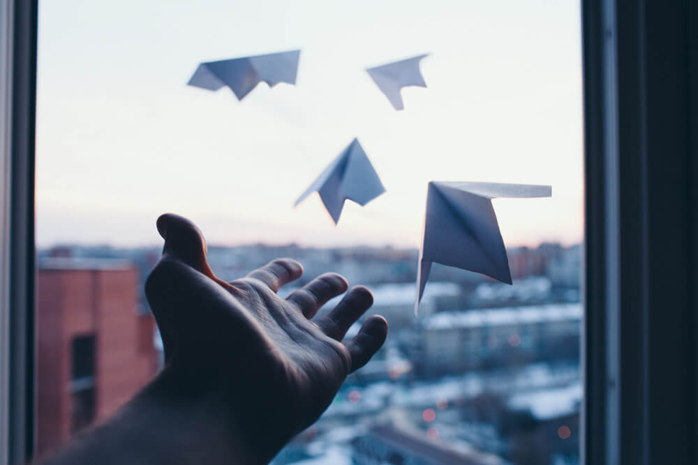 A man's hand launches paper aeroplanes representing Workday Go-Live